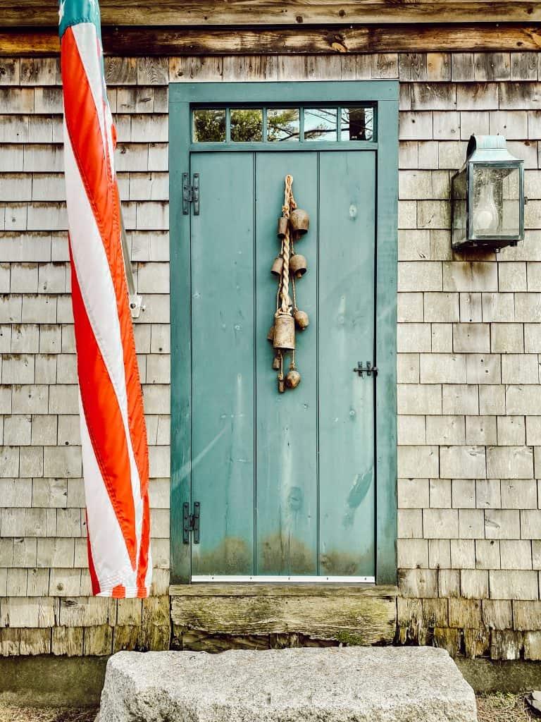 A door is open to a cedar shake home