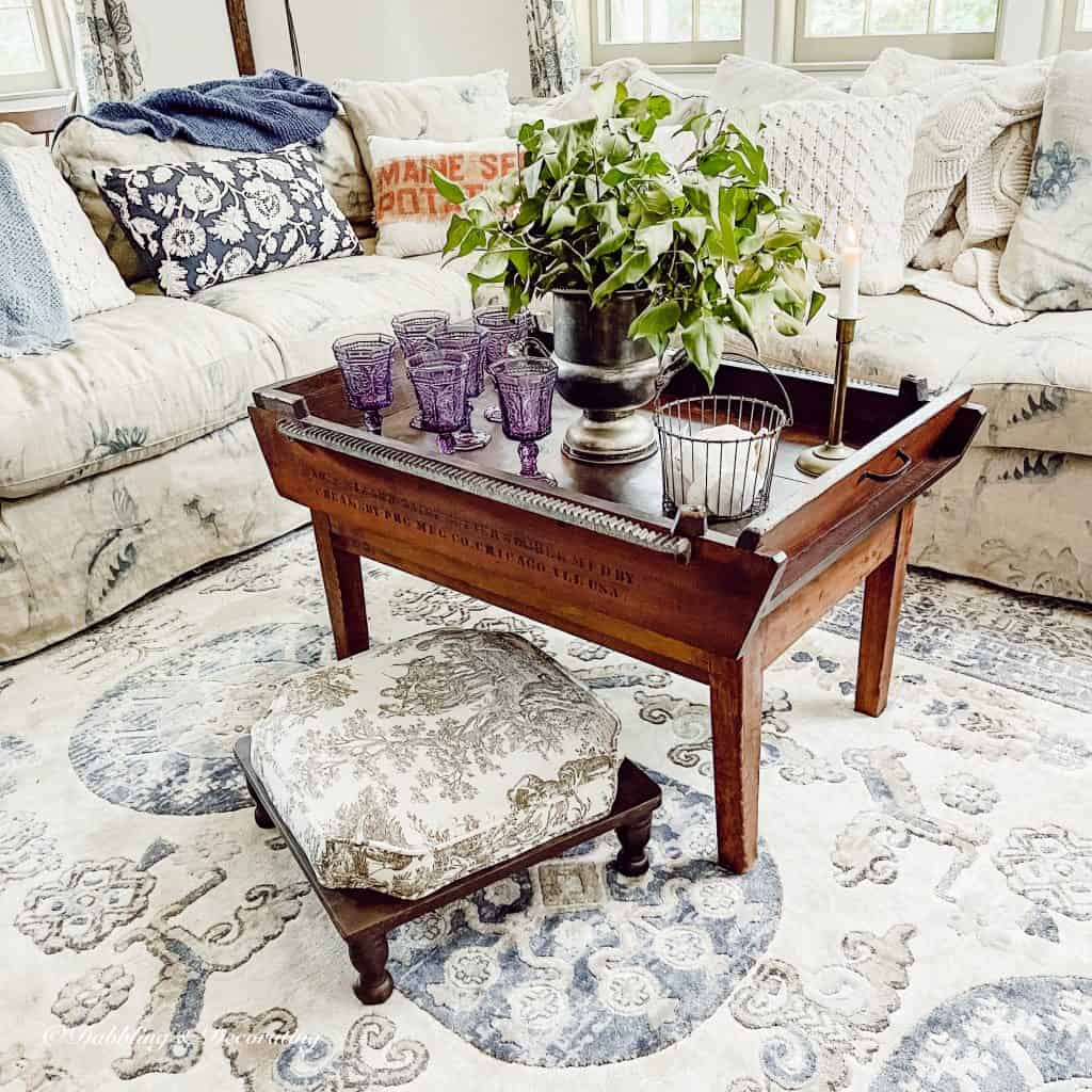 living room with antique coffee table and glasses.