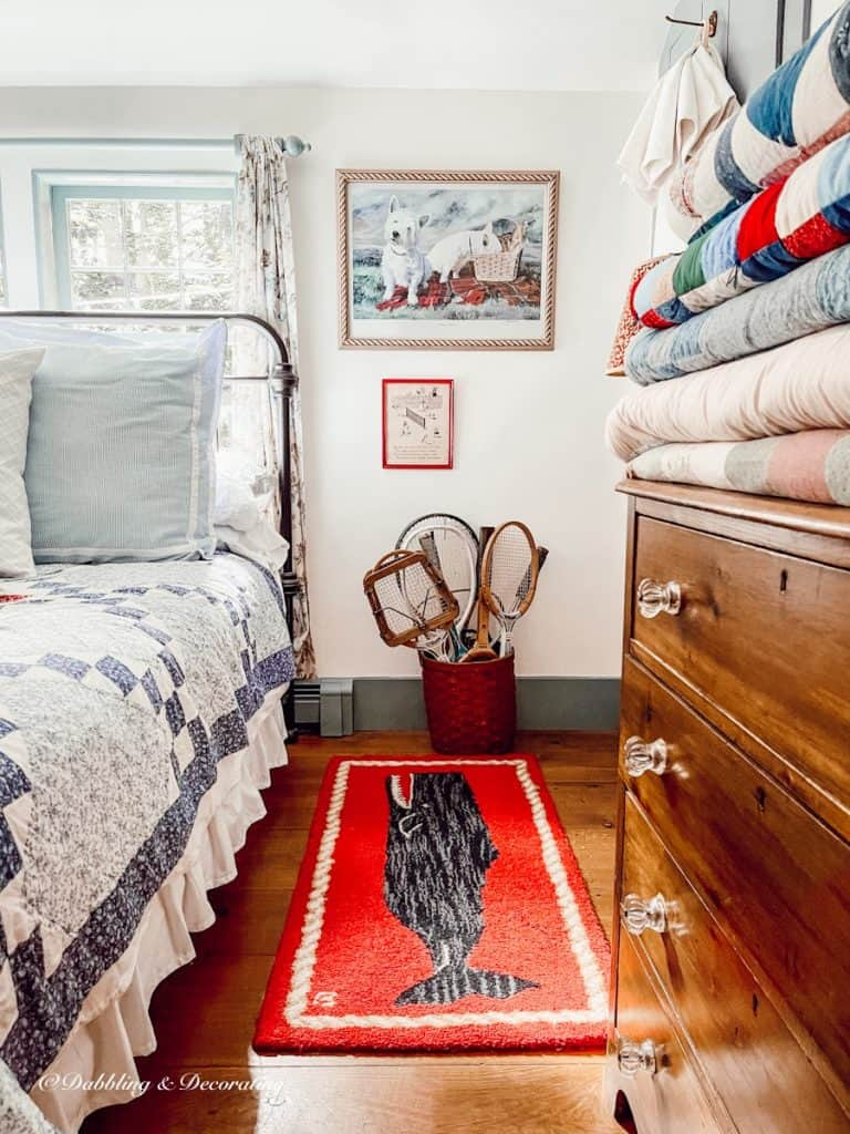 bedroom with quilts and basket of tennis racquets.