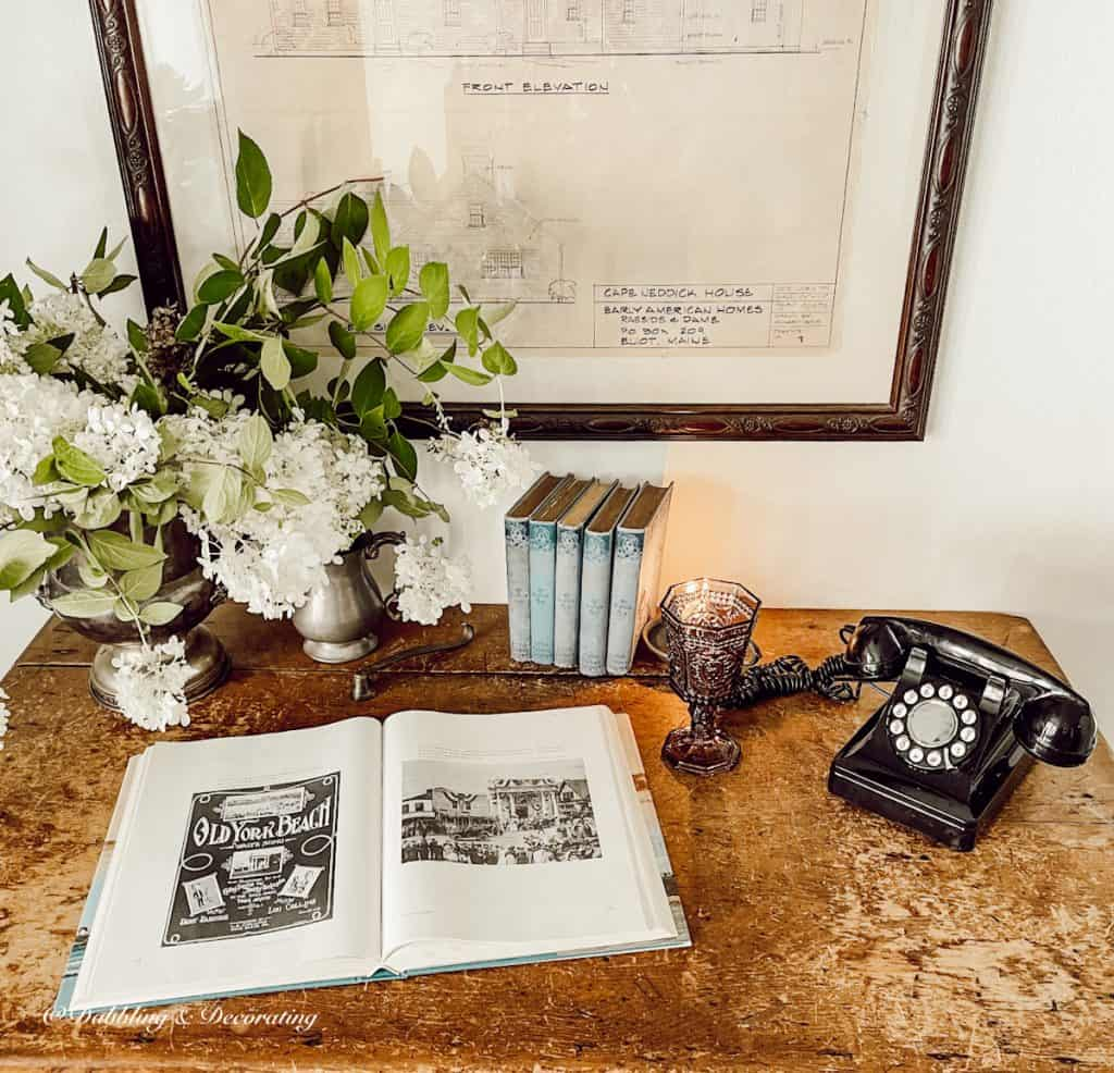 antique table with books, flowers, and telephone