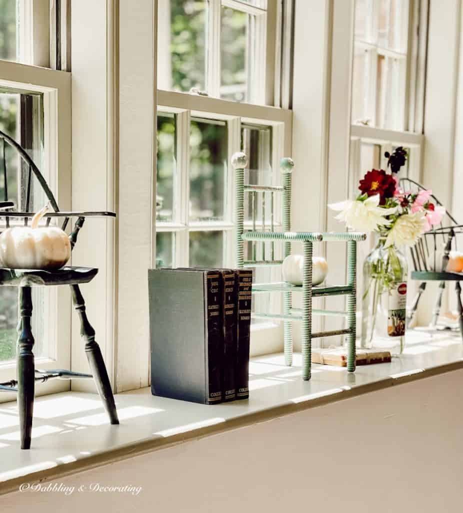windowsill with pumpkins and doll chairs.