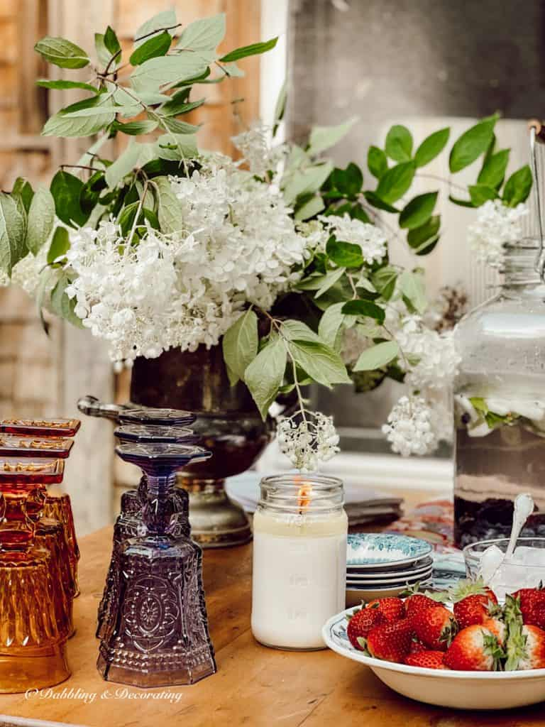 Beautiful glassware on an outdoor country table with strawberries.