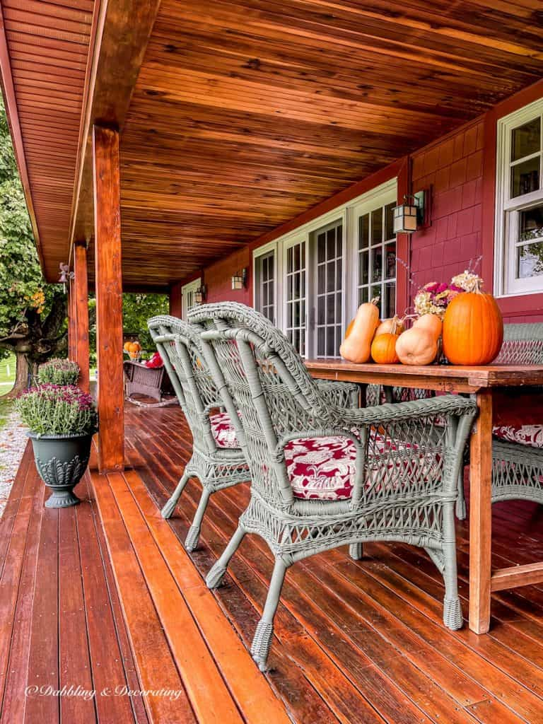 Long wooden porch with green urns